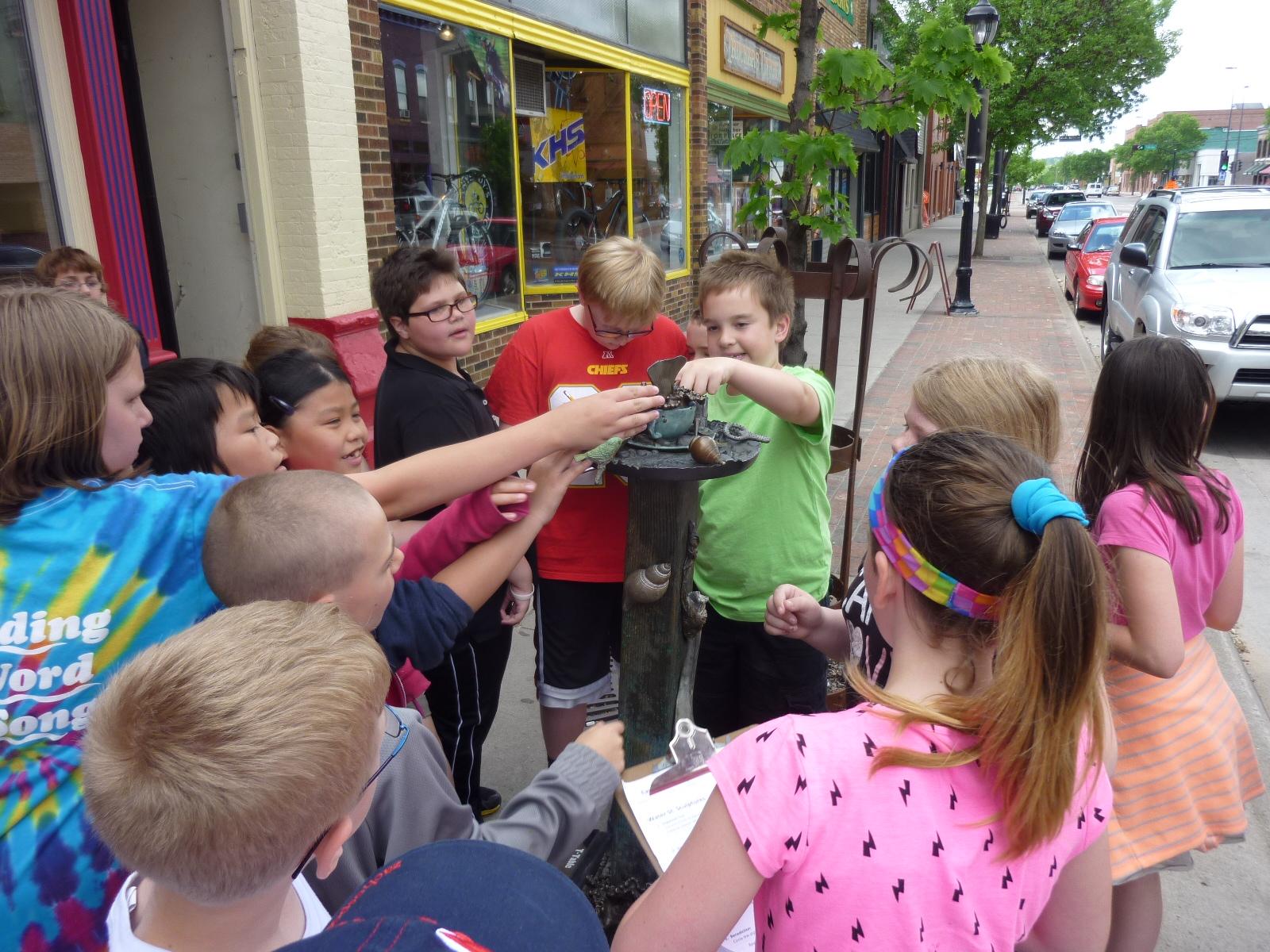 Children touching sculpture